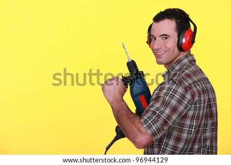 Man wearing protective ear muff and holding power drill - stock photo
