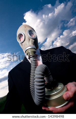 Man wearing respirator and black suit, standing against blue sky with clouds. He's handing air filter in right hand.