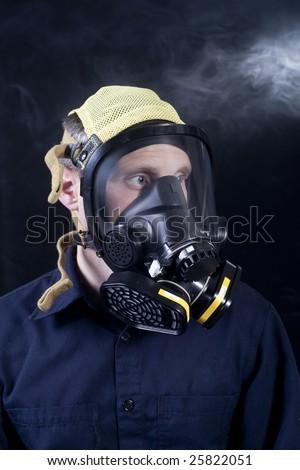 man wearing respirator or gas mask while exposed to toxic gas or smoke - stock photo