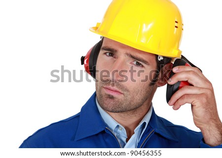 Man wearing safety earmuffs and helmet - stock photo