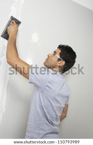 Man wearing safety goggles while applying putty on wall - stock photo
