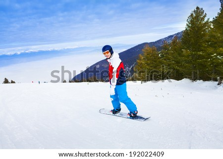 Man wearing ski mask standing on snowboard