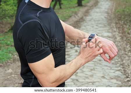 Man wearing smart watch preparing to run in park. Sport, jogging, healthy life style concept.  - stock photo