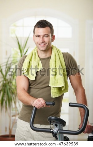 Man wearing sportswear and towel standing in living room at home with training bike, smiling. - stock photo