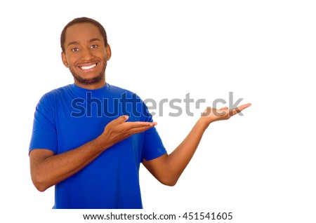 Man wearing strong blue t-shirt standing and interacting using hands simulating presentation while smiling, white studio background - stock photo