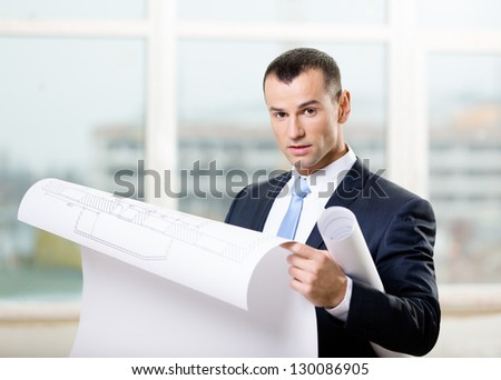 Man wearing suit and blue tie looks at blueprint in hands