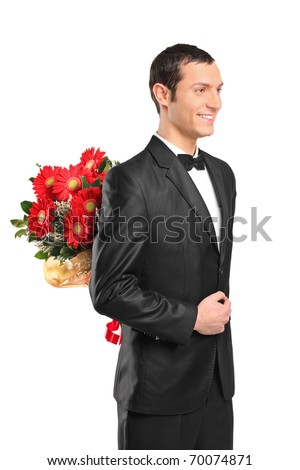 Man wearing suit and bow tie hiding a bouquet of flowers behind his back isolated on white background - stock photo