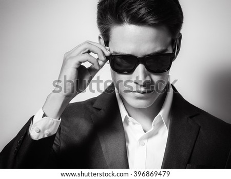 Man wearing sunglasses and a suit.  - stock photo