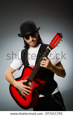 Man wearing sunglasses and playing guitar - stock photo
