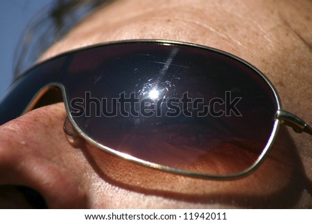 man wearing sunglasses and staring into sun - stock photo
