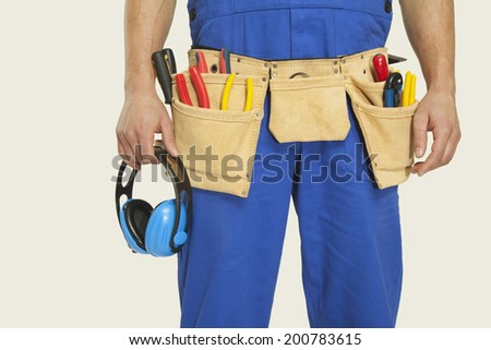 Man wearing tool belt and holding ear muff mid section close-up - stock photo