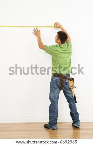 Man wearing tool belt measuring interior wall. - stock photo