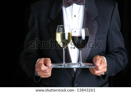 Man Wearing Tuxedo Holding Two Glasses of Wine on a Tray - stock photo