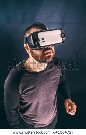 Man wearing virtual reality device, studio shot
