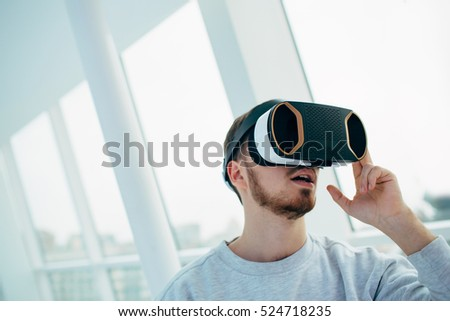 Man wearing virtual reality goggles. Studio shot, bright background. Vr.