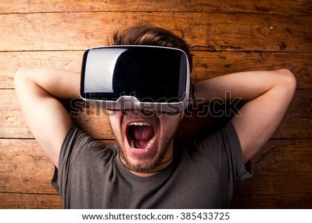Man wearing virtual reality goggles. Studio shot, wooden background - stock photo