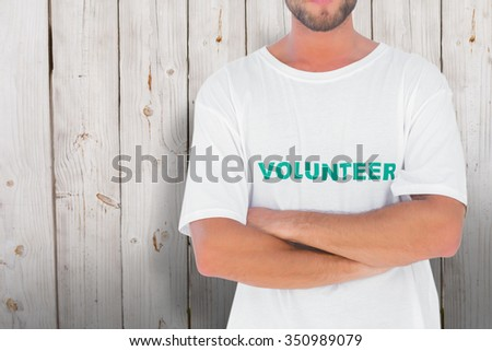 Man wearing volunteer tshirt with arms crossed against wooden background