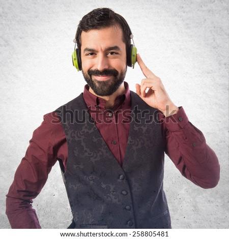 Man wearing waistcoat listening music over textured background  - stock photo