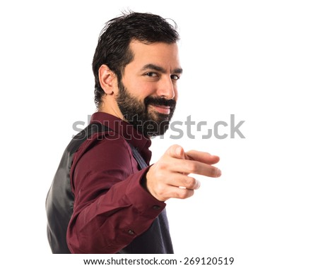 Man wearing waistcoat pointing to the front  - stock photo