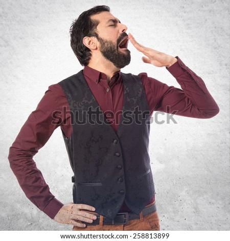 Man wearing waistcoat yawning - stock photo
