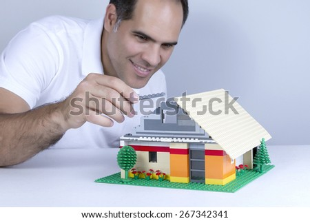 Man wearing white shirt smiles while assembling a house with small parts in plastic - stock photo