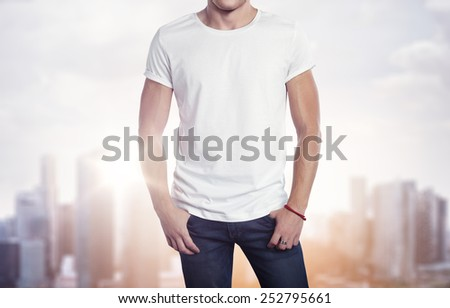 Man wearing white t-shirt on blurred city background - stock photo