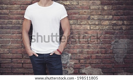 man wearing white t-shirt on brick wall background - stock photo