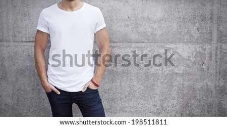 man wearing white t-shirt on bright concrete background - stock photo