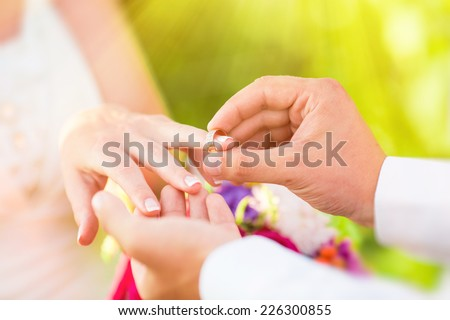 Man wears a ring on the finger of woman - stock photo