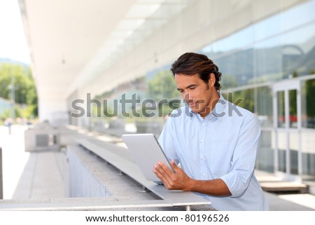 Man websurfing on electronic tablet outside - stock photo