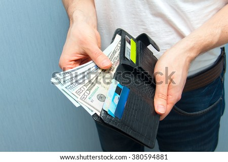 Man weeds off cash out of his wallet. Wealthy man counting his money