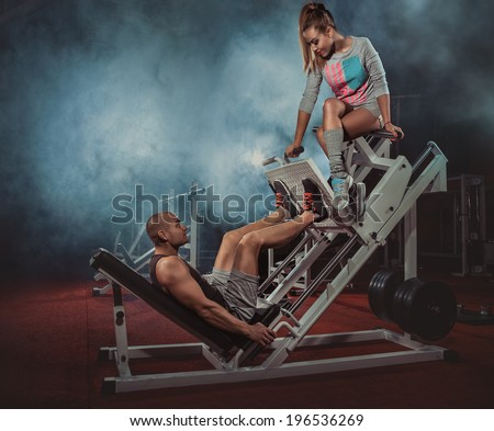 Man weightlifter doing leg presses with his trainer up on simulator  - stock photo