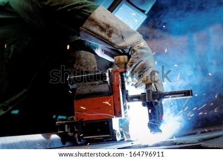 Man welding in factory closeup - stock photo