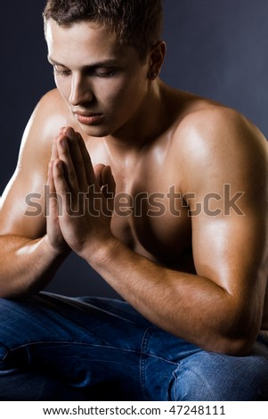 man which prays on black background