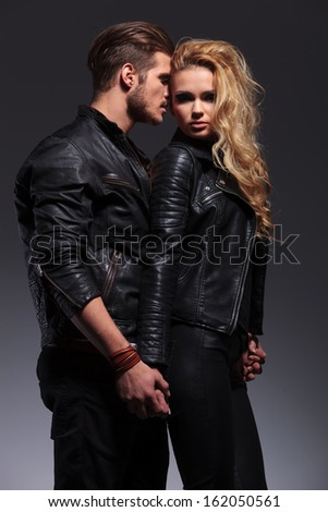 man whispering something to his girlfriend's ear while embracing her - stock photo