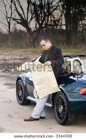 Man who has pulled off the road into an isolated area reading a map trying to figure out where he is. - stock photo