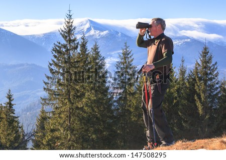 Man who is studying tourist route in the mountains - stock photo