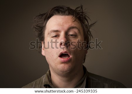 Man who just doesn't feel that awake and looks like he was sleeping at his desk. - stock photo