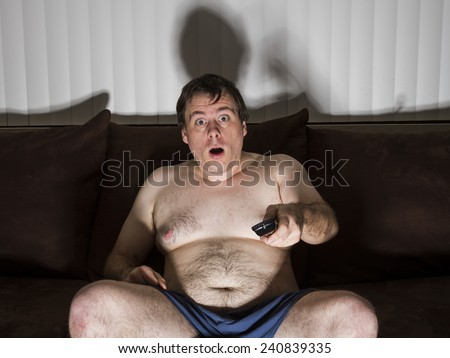 Man who needs to cut some weight doesn't get off the couch watching TV. - stock photo