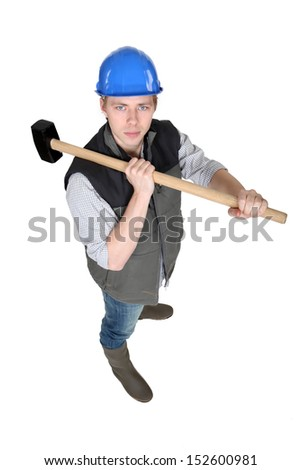 Man wielding heavy hammer - stock photo