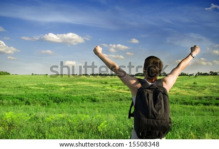 Man winner traveler on the meadow with green grass and blue sky - stock photo