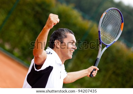 Man winning at tennis with arms up and holding a racket - stock photo