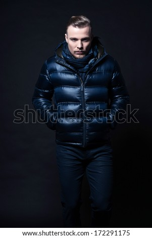 Man winter fashion. Wearing blue jacket and scarf. Blonde hair and beard. Studio shot against black.