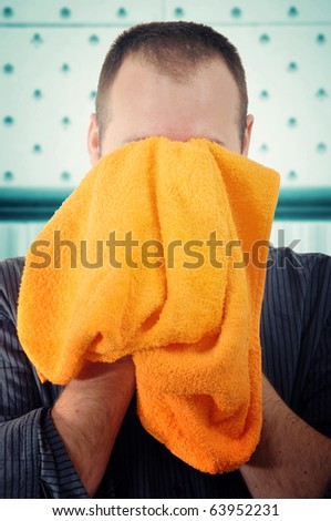 Man wiping face with orange towel in bathroom