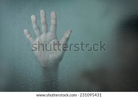 man witch standing in the shower room behind the wet glass. Artistic darkness and texture added - stock photo