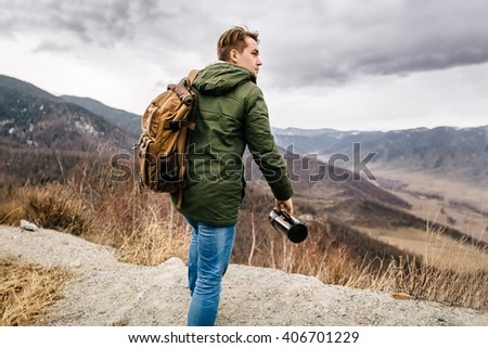 man with a backpack and thermos rises to the top of the mountain