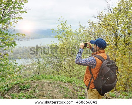 man with a backpack photographed on a smartphone natural landscape