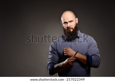 Man with a beard holding a pair of scissors - gray background - stock photo