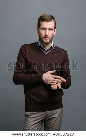 Man with a beard in a business casual clothes on a gray background in the studio, gestures, thoughts, doubts, solutions
