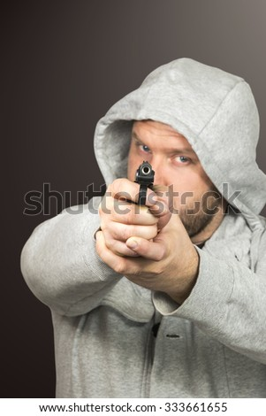 Man with a beard wearing a jacket with a hood holds a gun aimed at the camera